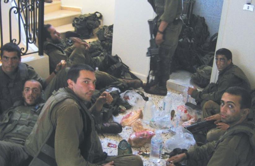 BENYAMIN BEN-ARI (third from left, foreground) and his buddies eat lunch in south Lebanon 10 years ago. (photo credit: COURTESY BENYAMIN BEN-ARI)