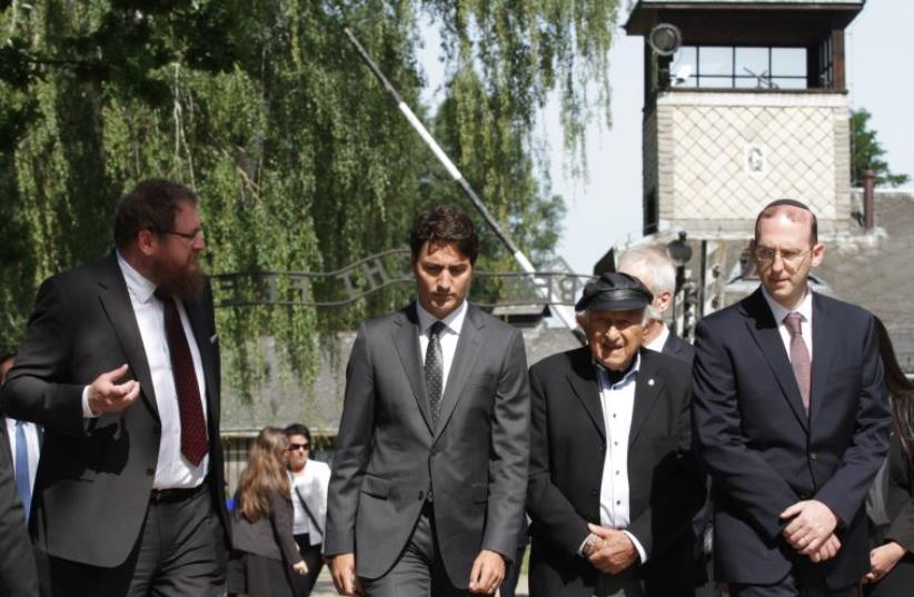Canadian Prime Minister Justin Trudeau (2nd L) is accompanied by the director of the Auschwitz Museum Piotr Cywinski (L) and Holocaust survivor Nate Leipciger (2nd R) as he visits the site of the former German Nazi concentration camp  (photo credit: STANSILAW ROZPEDZIK/PAP/AFP)