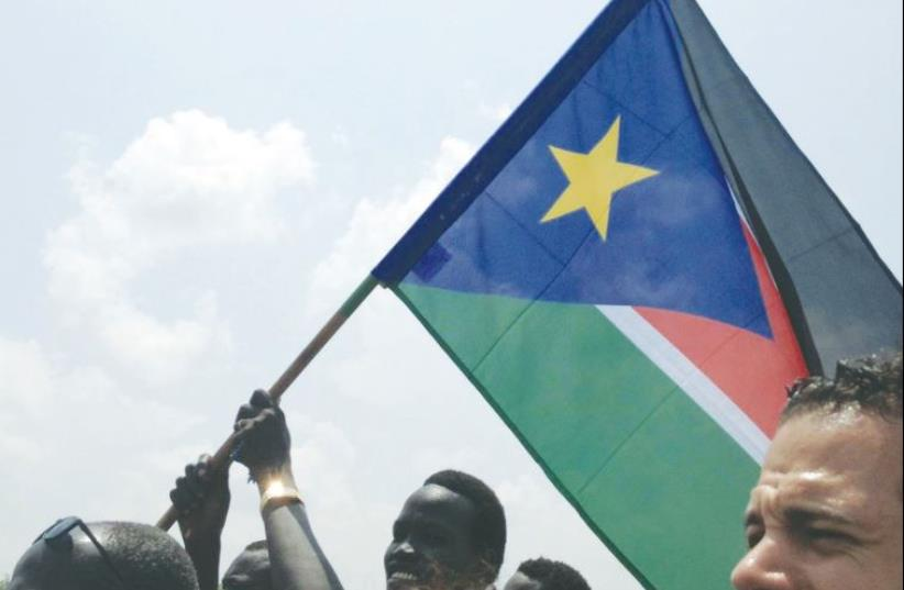 A PROUD CITIZEN waves the South Sudan flag at a pro-government demonstration on Monday, the same day the Israel Forum for International Humanitarian Aid (IsraAID) became trapped by the local internecine conflict. (photo credit: ISRAAID)