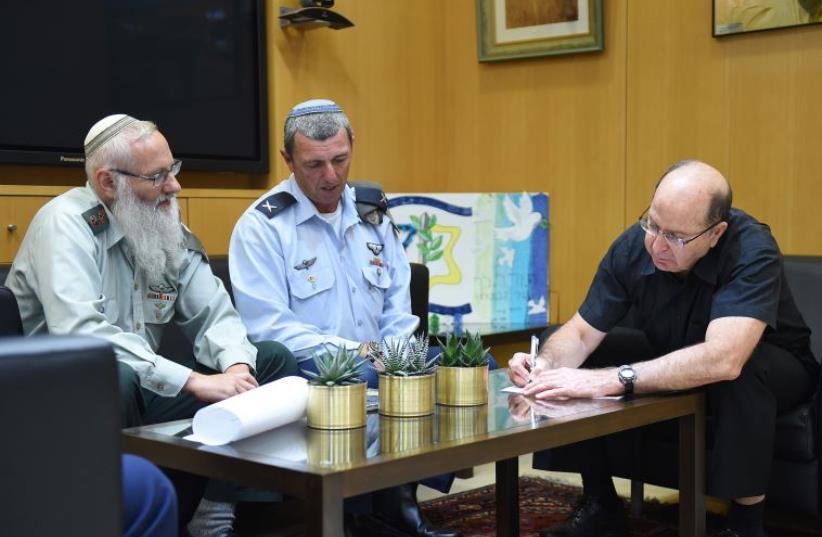 Rabbi Col. Eyal Karim (left), nominated to become IDF chief rabbi, sits next to his predecessor, Bri (photo credit: DEFENSE MINISTRY/DIANA HANANSHIVILI)