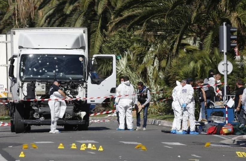Investigators continue at the scene near the heavy truck that ran into a crowd at high speed killing scores who were celebrating the Bastille Day July 14 national holiday on the Promenade des Anglais in Nice, France, July 15, 2016.  (photo credit: REUTERS/ERIC GAILLARD)