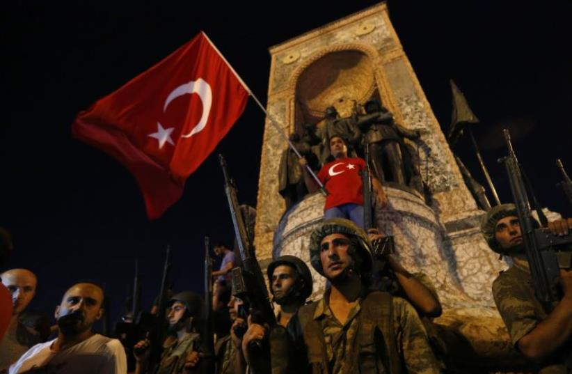 Turkish military stand guard near the the Taksim Square as people wave with Turkish flags in Istanbul, Turkey, July 16, 2016 (photo credit: REUTERS)