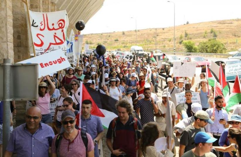 Israelis and Palestinians marching next to the separation barrier on their way to the Tunnels Checkpoint. (photo credit: COMBATANTS FOR PEACE)