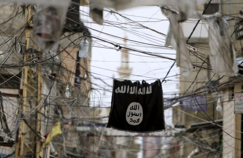 An Islamic State flag hangs amid electric wires over a street (photo credit: REUTERS)