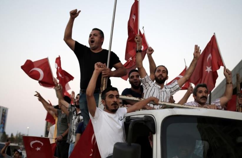 Supporters of Turkish President Tayyip Erdogan shout slogans on the back of a truck during a pro-government demonstration on Taksim square in Istanbul, Turkey, July 16, 2016 (photo credit: REUTERS)