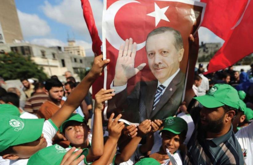 PALESTINIANS HOLD a poster of President Tayyip Erdogan during a demonstration yesterday in Gaza in support of the Turkish government. (photo credit: REUTERS)