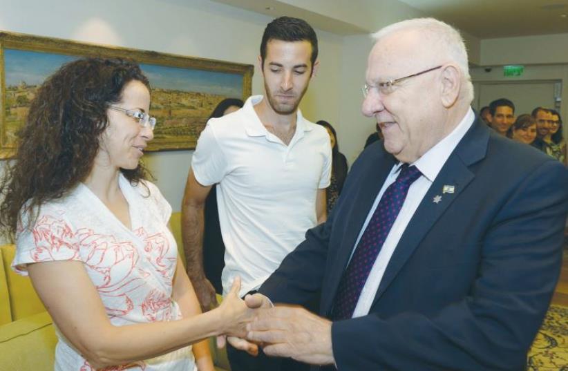 PRESIDENT REUVEN RIVLIN greets Mika Banki, mother of Shira Banki, at the President's Residence yesterday. (photo credit: GPO)
