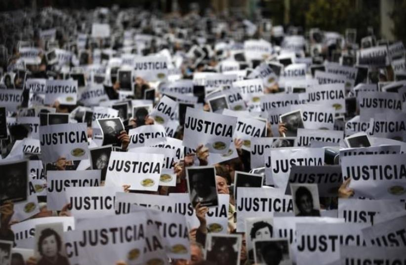 """DATE IMPORTED: July 18, 2013 Thousands of people hold up signs reading, """"Justice"""" as they gather to commemorate the 19th anniversary of the 1994 bombing of the Argentine Israeli Mutual Association (AMIA) Jewish community center in Buenos Aires July 18, 2013. (photo credit: REUTERS/MARCOS BRINDICCI)"""