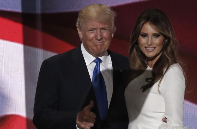 Republican US presidential candidate Donald Trump gives a thumbs up with his wife Melania. (photo credit: MIKE SEGAR / REUTERS)
