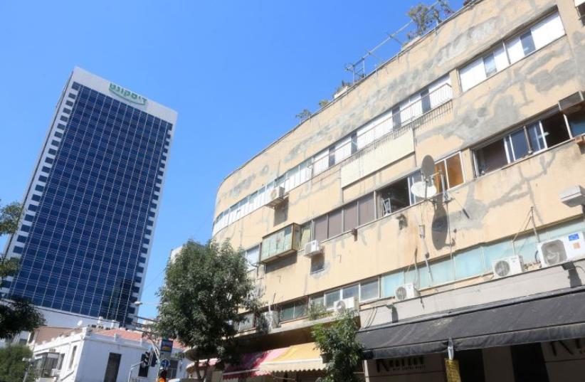 Discount Bank high rise stands next tot dilapidated building in Tel Aviv (photo credit: REUTERS)