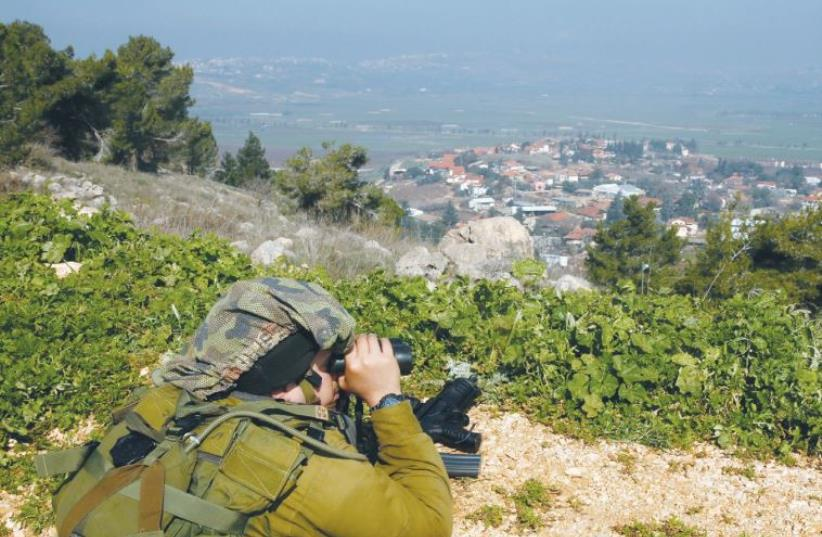 A SOLDIER near Metulla monitors Lebanon (photo credit: REUTERS/BAZ RATNER)