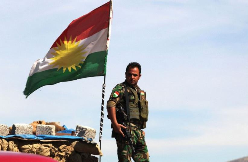 A KURDISH peshmerga soldier stands at a lookout near Bashiqa in northern Iraq (photo credit: REUTERS)