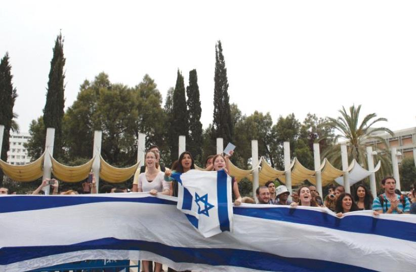 STUDENTS WAVE flags at an event at Tel Aviv University. (photo credit: REUTERS)