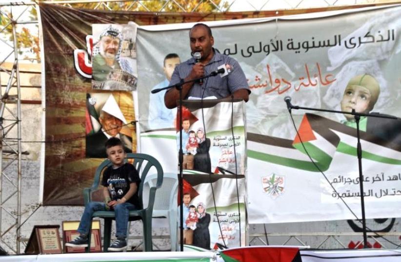 Nasr Dawabsha addresses rally in Duma and his nephew, Ahmad Dawabsha, sits by his side (photo credit: TOVAH LAZAROFF)