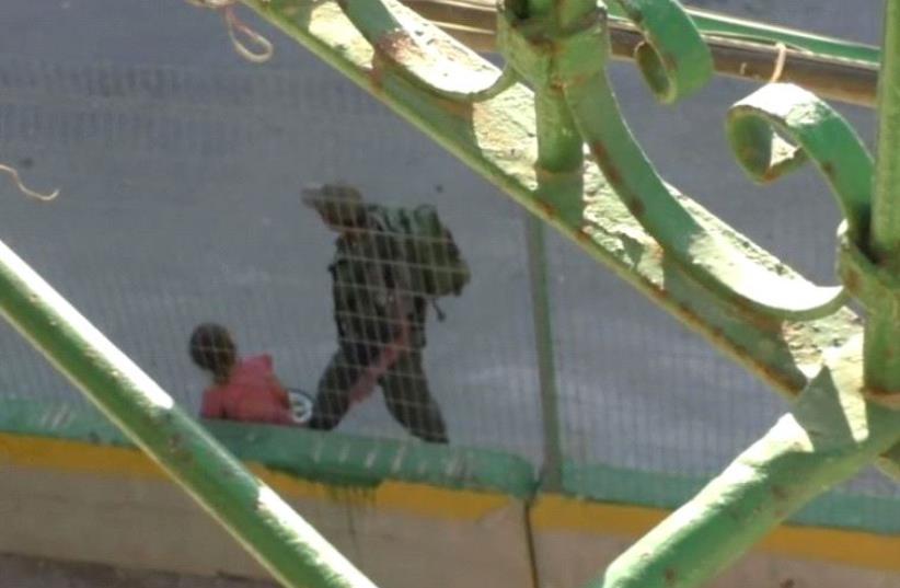 Screenshot of B'tselem video in which Border Policeman seen confiscating Palestinian girl's bike (photo credit: screenshot)
