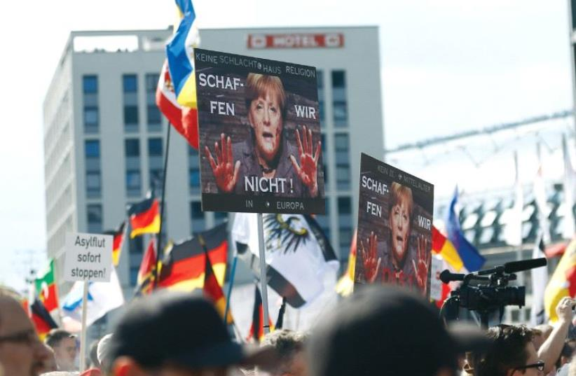 Participants of the right-wing demonstration 'Wir für Berlin und Wir für Deutschland' ('We for Berlin and We for Germany') protest in Berlin on July 30. The text on placard reads 'We cannot do this!' (photo credit: REUTERS)