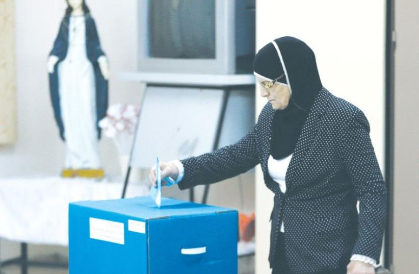 AN ISRAELI ARAB casts her vote at a polling station inside a church in the northern village of Reina on March 17, 2015. (photo credit: REUTERS)