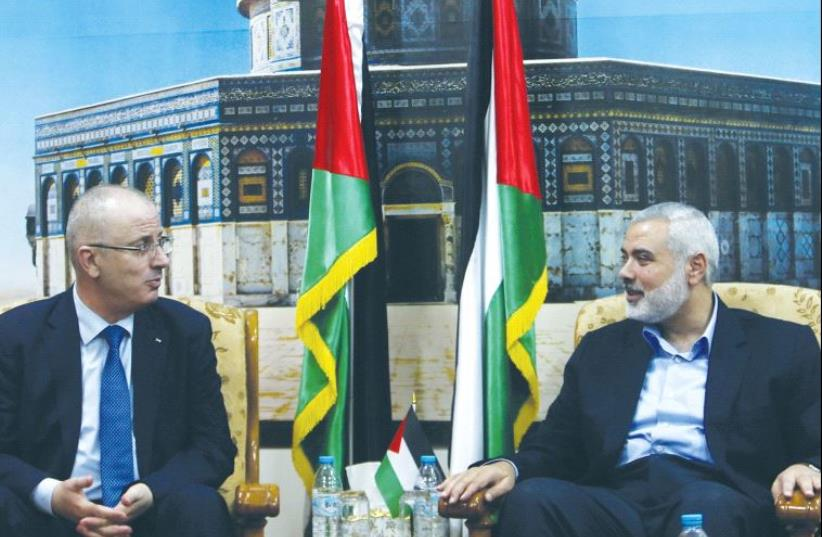 SENIOR HAMAS leader Ismail Haniyeh meets with Palestinian Prime Minister Rami Hamdallah at Haniyeh's house in Gaza City in 2014. (photo credit: REUTERS)