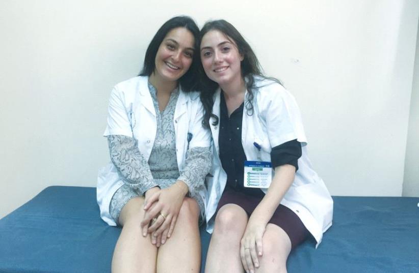 NATIONAL SERVICE VOLUNTEERS Annaelle Dabi (left) and Johanna Arrouas take a break at Sheba Medical Center in Tel Hashomer last week. (photo credit: TAMARA ZIEVE)