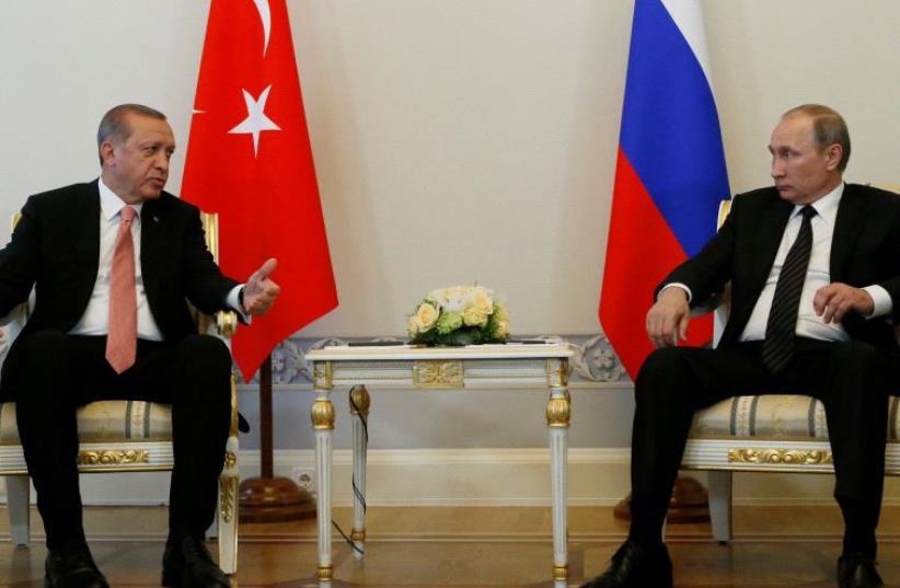 Turkish President Tayyip Erdogan speaks to Russian President Vladimir Putin (R) during their meeting in St. Petersburg, Russia, August 9, 2016 (photo credit: REUTERS)