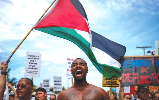 DEMONSTRATORS WAVE the Palestinian flag during a march by various groups, including Black Lives Matter, ahead of the Republican National Convention in Cleveland, in July. / ADREES LATIF/REUTERS