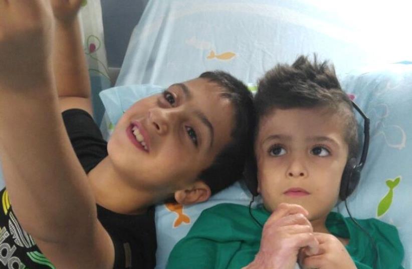 Ahmad Dawabsha at Shebaa Hospital with cousin (photo credit: NASR DAWABSHA)