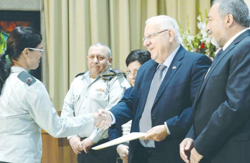 Maj. Sigal Turgeman shakes hands with President Reuven Rivlin in Jerusalem, as Defense Minister Avigdor Liberman, Supreme Court President Miriam Naor and Chief of Staff Gadi Eisenkot look on (photo credit: MARK NEYMAN / GPO)