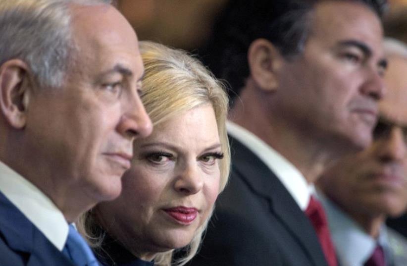 Sara Netanyahu sitting next to Prime Minister Benjamin Netanyahu  (photo credit: BRENDAN SMIALOWSKI / AFP)
