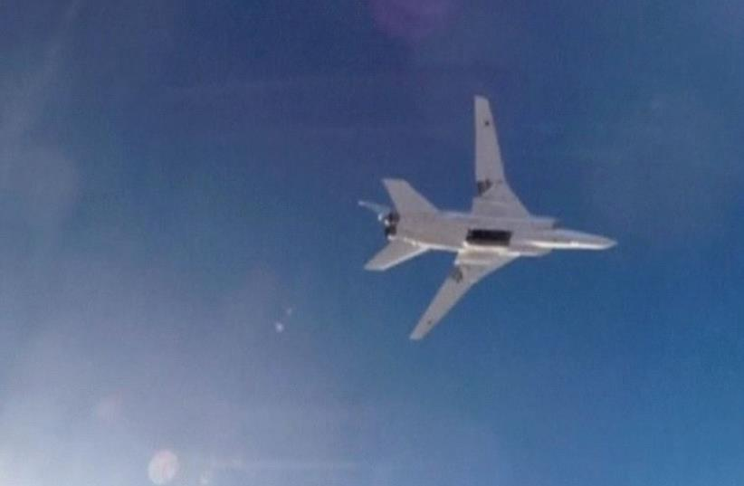 A STILL IMAGE taken from video shows a Russian Tupolev Tu-22M3 long-range bomber based in Iran flying over an unknown location in Syria on Tuesday after dropping its payload. (photo credit: RUSSIAN DEFENSE MINISTRY)