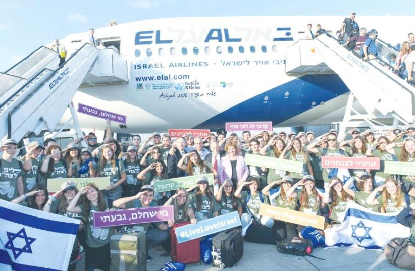 New immigrants pose for a photo with Immigration and Absorption Minister Sofa Landver (center, in pink blazer) yesterday upon arriving at Ben-Gurion Airport. (photo credit: SHAHAR AZRAN)