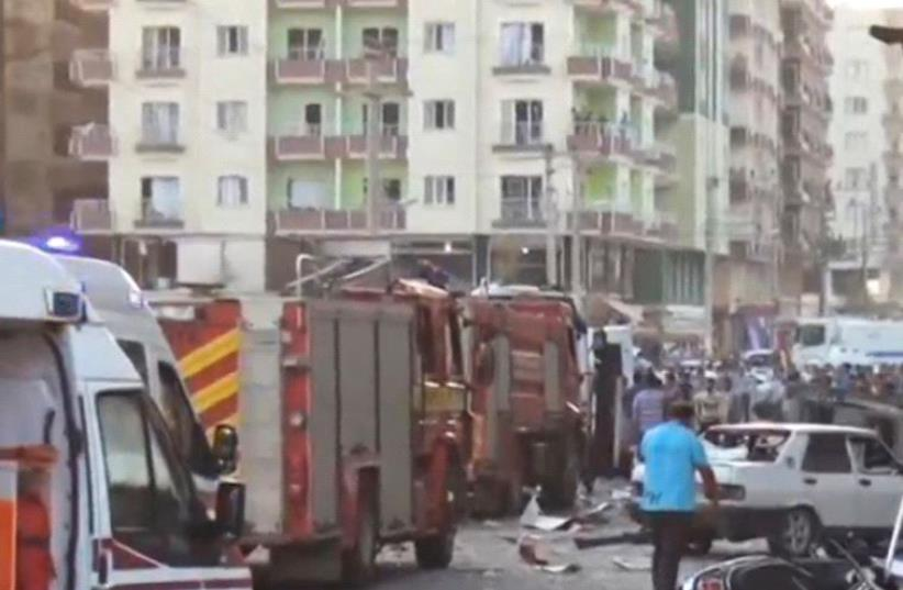 A still image taken from a video footage shows emergency vehicles at the scene of a bomb blast in Kiziltepe, Turkey (photo credit: REUTERS)
