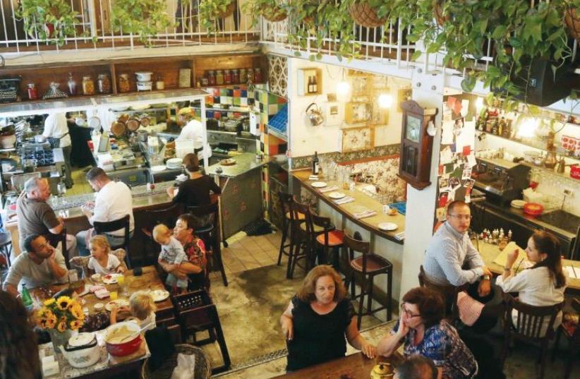 Diners enjoy a meal at the Machneyuda restaurant (non-kosher) in Jerusalem (photo credit: MARC ISRAEL SELLEM)