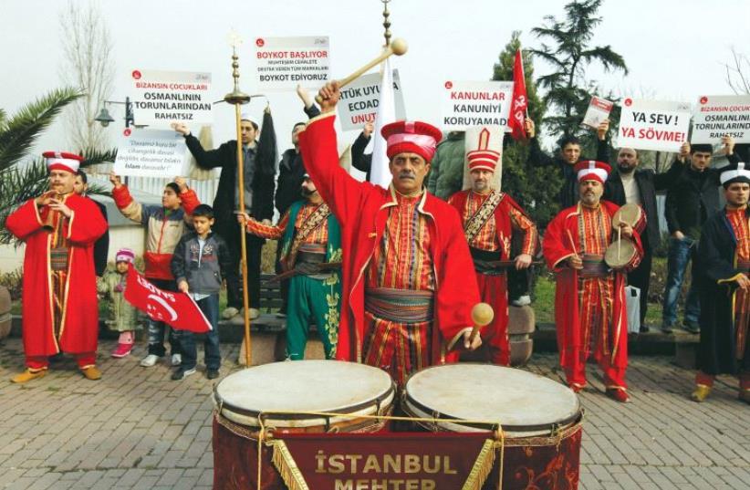 Men dressed up in Ottoman era garb pound on a drum (photo credit: REUTERS)