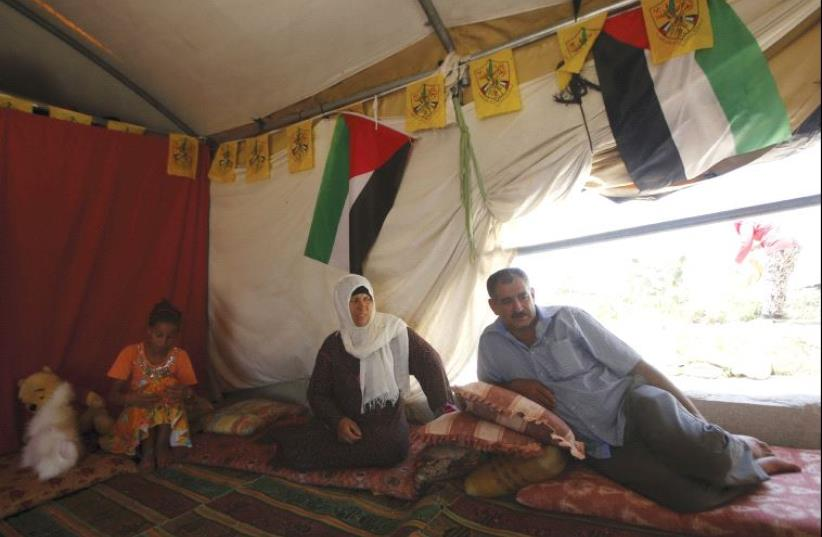 A man sits with his family inside their tent in Sussiya (photo credit: MUSSA QAWASMA / REUTERS)