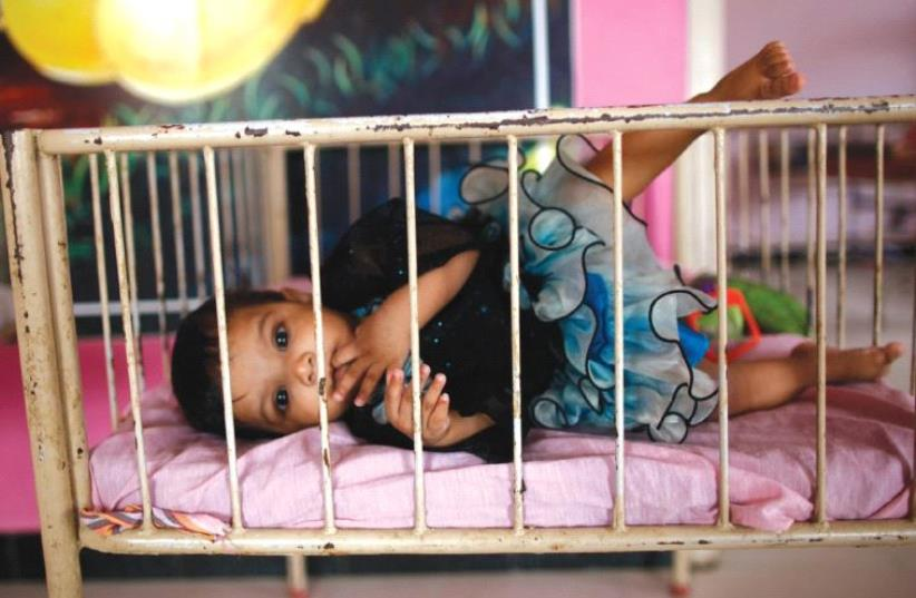 A BABY lies in her crib in this illustrative photo. ( (photo credit: REUTERS)