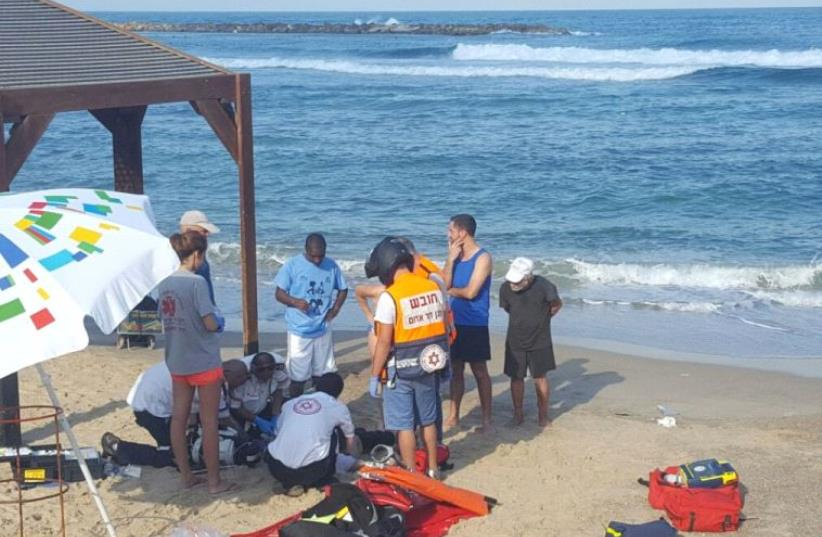 Magen David Adom paramedics treating a man on Tel Aviv's Hilton Beach.  (photo credit: MAGEN DAVID ADOM)