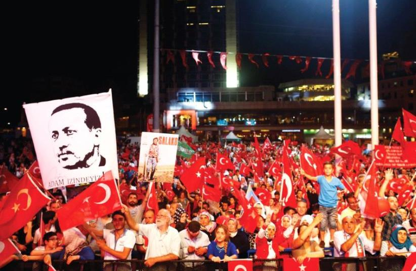 SUPPORTERS OF Turkish President Recep Tayyip Erdogan wave national flags in Taksim Square (photo credit: REUTERS)