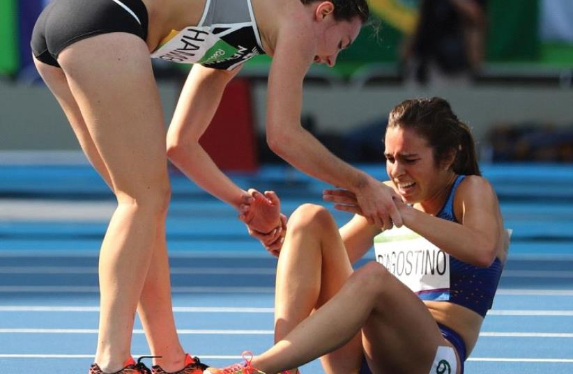 Nikki Hamblin of New Zealand stops running during the race to help fellow competitor Abbey D'Agostino (US) (photo credit: REUTERS)