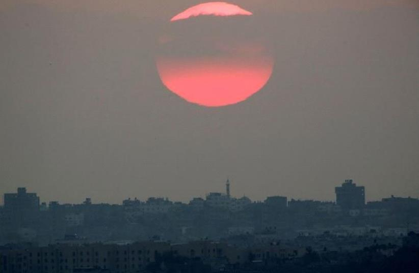The sun sets over the northern Gaza Strip as seen from the Israeli border, Israel August 23, 2016 (photo credit: REUTERS)