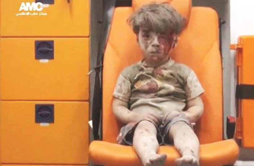 Le petit Omran sorti ensanglanté des décombres de sa maison (photo credit: REUTERS)