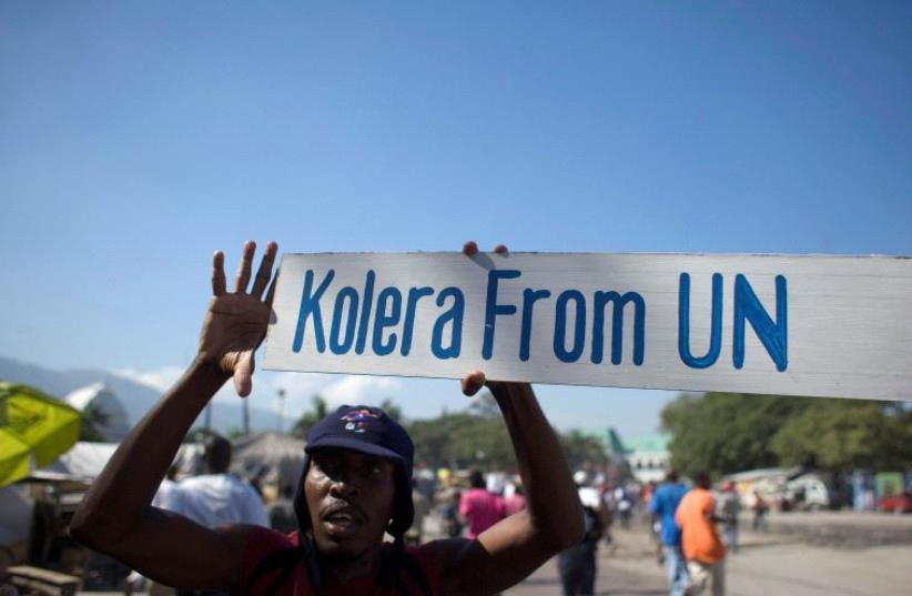 A protester holds up a sign during a demonstration against the UN mission in downtown Port-au-Prince November 18, 2010 (photo credit: REUTERS)