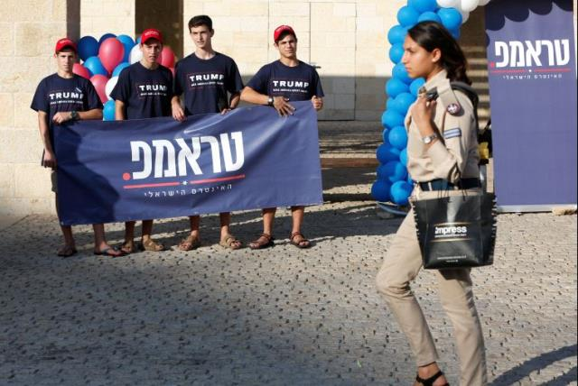 An Israeli soldier walks past members of the US Republican party's election campaign team in Israel, who are holding a banner in support of Republican US presidential nominee Donald Trump, during a campaign aimed at potential American voters living in Israel, near a mall in Modi'in, Israel. (photo credit: REUTERS)