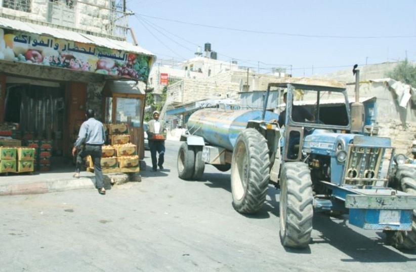A TRACTOR carries water in the village of Sa'ir earlier this month. (photo credit: TOVAH LAZAROFF)
