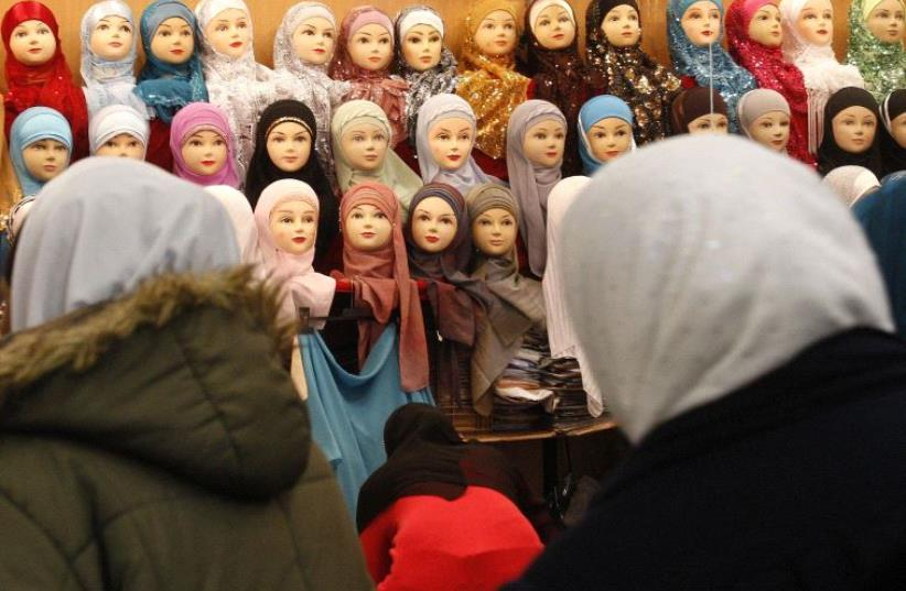 Women look at headgear of Muslim women inside an exhibition hall s at Le Bourget (photo credit: REUTERS)