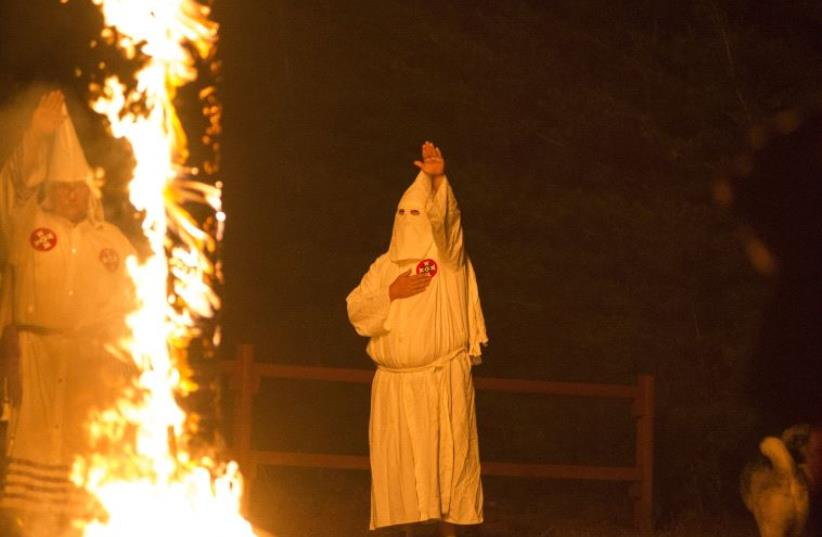 A member of the Ku Klux Klan salutes a lit cross during a cross lighting ceremony. (photo credit: REUTERS)