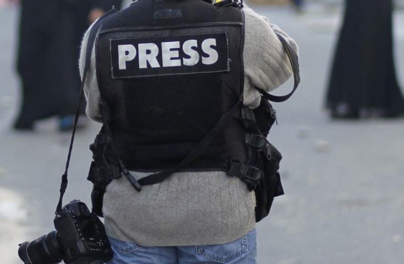 A photojournalist in a press vest [Illustrative] (photo credit: REUTERS)