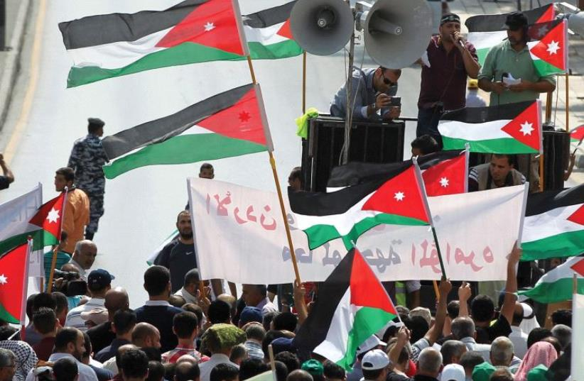 PROTESTERS IN Jordan hold Jordanian and Palestinian flags as they march in protest against Israel. (photo credit: REUTERS)