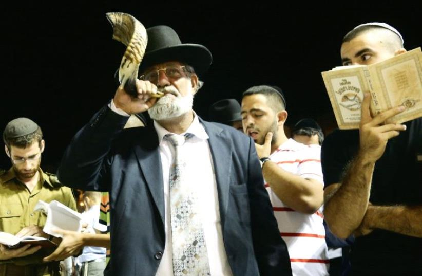 A man blows a shofar while others read 'slihot' during the Days of Awe at the Western Wall (photo credit: MARC ISRAEL SELLEM)