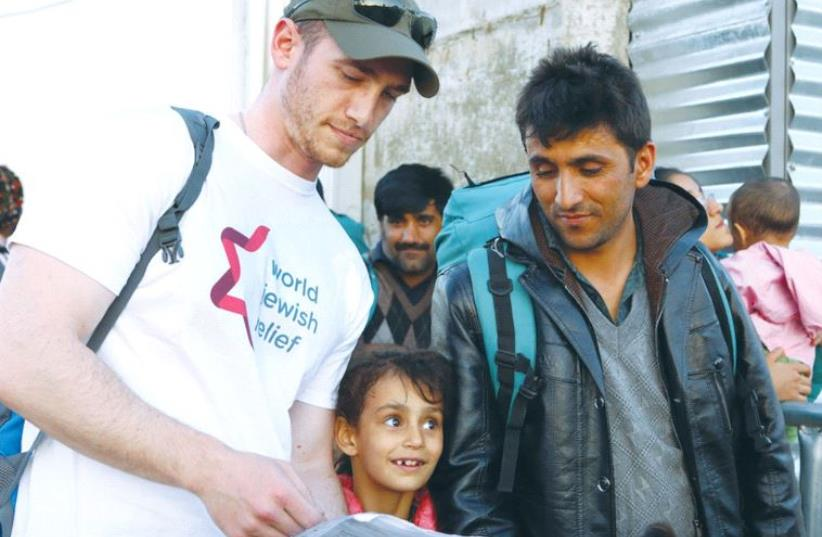 AN AID WORKER speaks with refugees in Greece in 2015. ( (photo credit: WORLD JEWISH RELIEF)