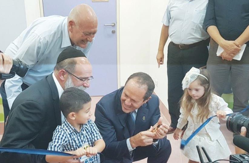 ERUSALEM MAYOR Nir Barkat (right) joins Shalva founder Rabbi Kalman Samuels and two children in cutting the ribbon for the kindergarten at the organization's new complex in Jerusalem's Beit Hakerem neighborhood. (photo credit: SHALVA)
